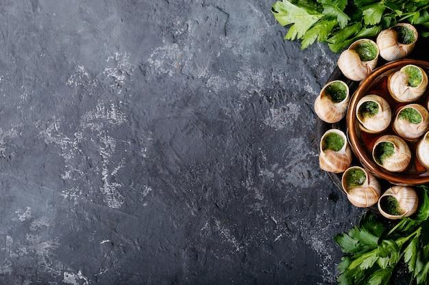 Запеченные улитки с чесночным маслом и свежей зеленью на сковороде, выборочный фокус