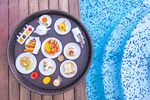 パンフルーツエッグコーヒーとジュースのある屋外スイミングプールの周りに浮かぶ朝食トレイ