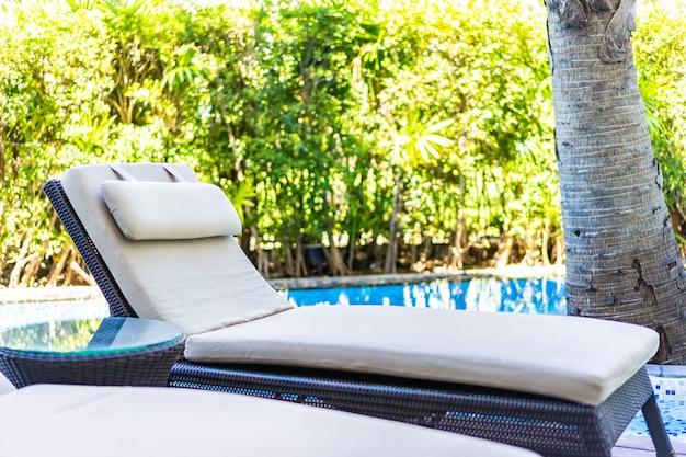 ホテルリゾートのスイミングプールの周りの空の椅子デッキラウンジ