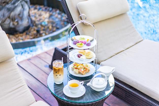 プールの周りの椅子の近くのテーブルでラテコーヒーと熱いお茶とアフタヌーンティーセット