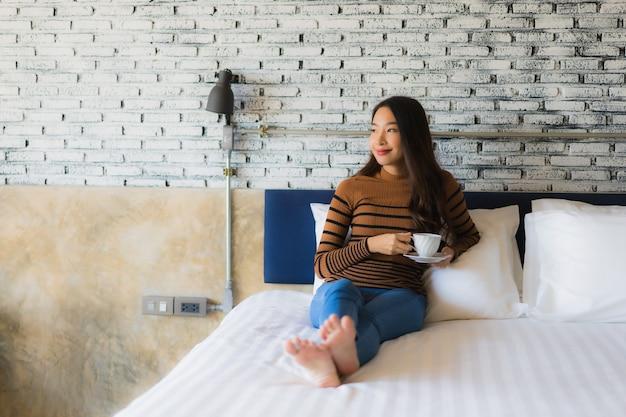 Молодая азиатская женщина с кофейной чашкой на кровати