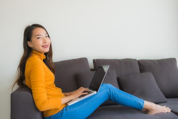 Женщина портрета молодая азиатская используя блокнот портативного компьютера на софе