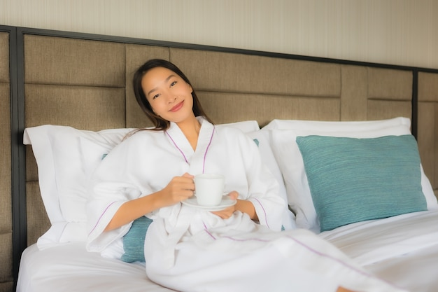 ベッドの上のコーヒーカップと美しい若いアジア女性の肖像画