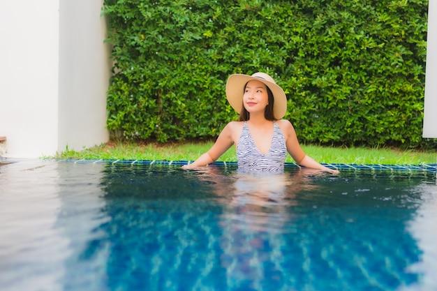 肖像画美しい若いアジア女性の幸せな笑顔はホテルリゾートの屋外スイミングプールの周りでリラックスします。