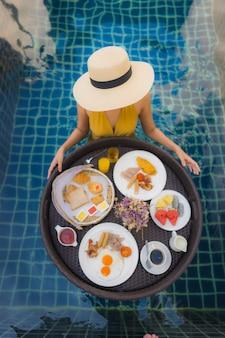 肖像画美しい若いアジア女性の幸せな笑顔は、スイミングプールの周りに浮かぶ朝食でリラックスします。