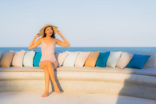 Улыбка красивой молодой азиатской женщины портрета счастливая вокруг пляжа океана моря