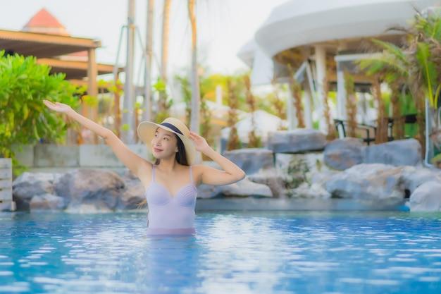 Улыбка красивой молодой азиатской женщины портрета счастливая ослабляет вокруг открытого бассейна в курорте гостиницы