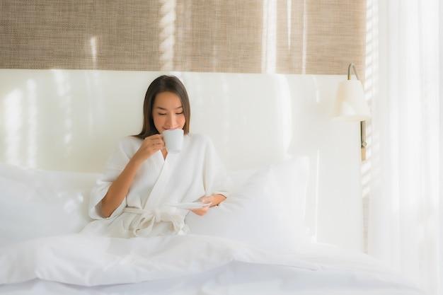 Улыбка красивой молодой азиатской женщины портрета счастливая с кофейной чашкой на кровати