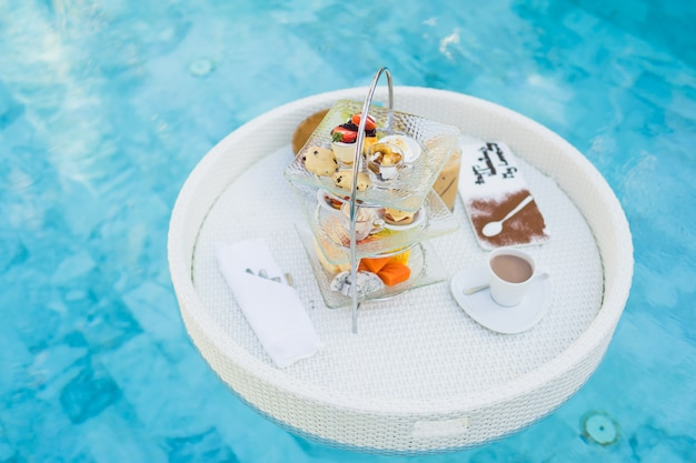 Завтрак и послеобеденный чайный сервиз, плавающие вокруг бассейна