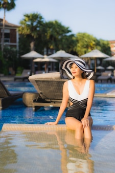 美しい肖像若いアジア女性の幸せな笑顔はリゾートホテルのスイミングプールの周りでリラックスします。