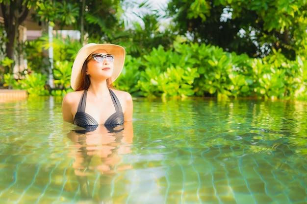 肖像画の美しい若いアジアの女性は、レジャー休暇のためにホテルリゾートのスイミングプールでリラックスします。