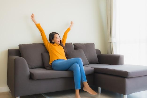 肖像若いアジア女性幸せなリビングルームで枕とソファ椅子に笑顔をリラックスします。