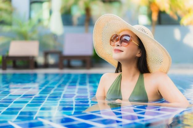 肖像画の美しい若いアジア女性はホテルリゾートのスイミングプールの周りでリラックスします。