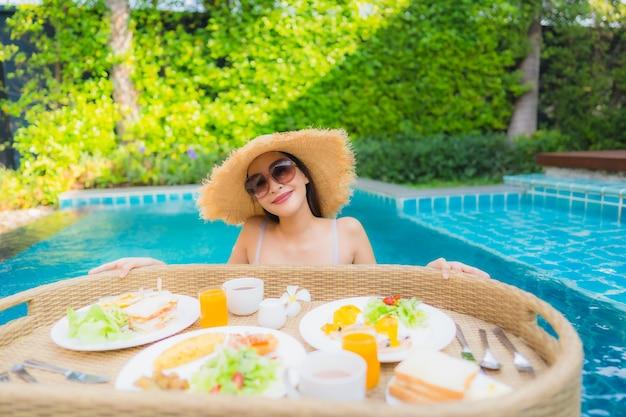 Улыбка молодой азиатской женщины портрета счастливая наслаждается с плавая подносом завтрака в бассейне в гостинице
