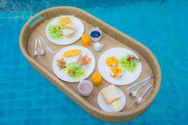 屋外スイミングプールの周りに浮かぶ朝食