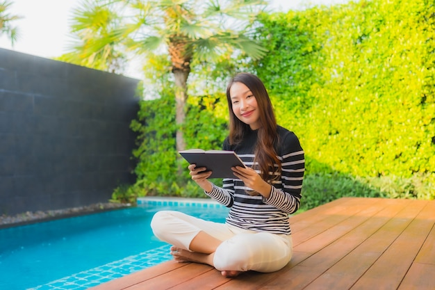 Женщина портрета молодая азиатская прочитала книгу вокруг открытого бассейна