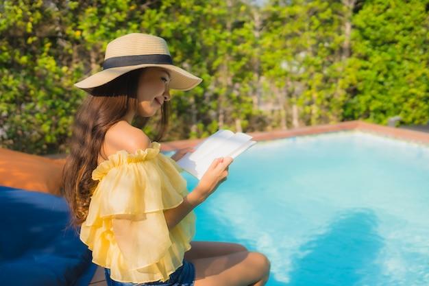 肖像若いアジア女性は屋外スイミングプールの周りの本を読む