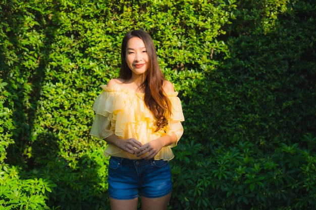 Улыбка молодой азиатской женщины портрета счастливая ослабляет вокруг напольного сада природы
