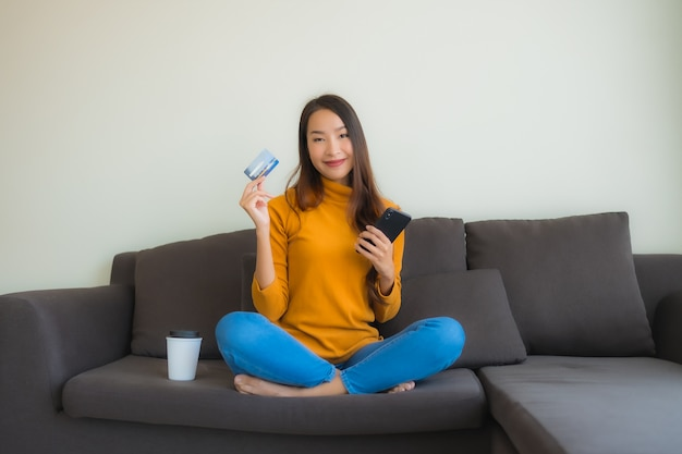 Женщина портрета молодая азиатская используя портативный компьютер с умным мобильным телефоном и кредитную карточку для покупок онлайн