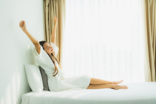 若いアジア女性の幸せな笑顔が寝室のベッドでリラックスします。