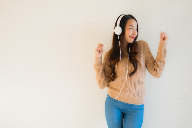 肖像画の美しい若いアジア女性は音楽を聴いて楽しんで幸せ