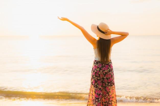 Улыбка красивых молодых азиатских женщин портрета счастливая ослабляет вокруг океана моря пляжа