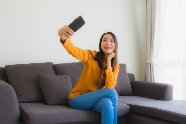 Женщина портрета молодая азиатская используя умный мобильный телефон на софе с подушкой в живущей комнате