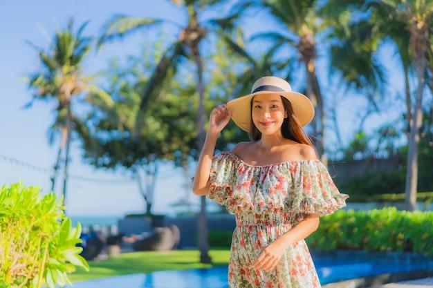 Улыбка красивой молодой азиатской женщины портрета счастливая ослабляет вокруг тропического океана моря пляжа