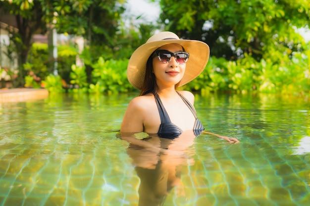 肖像画の美しい若いアジア女性はレジャー休暇のホテルリゾートのスイミングプールでリラックスします。