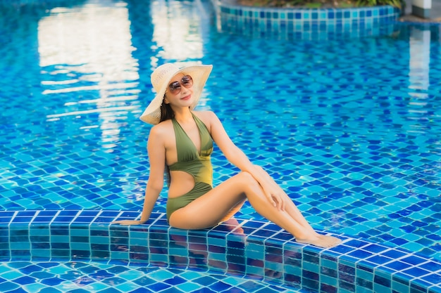 Женщина портрета красивая молодая азиатская ослабляет вокруг бассейна в курорте гостиницы