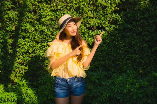 肖像画の若いアジア女性の幸せな笑顔は屋外の自然庭園の周りリラックスします。