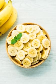 Сырые желтые кусочки банана в деревянной миске