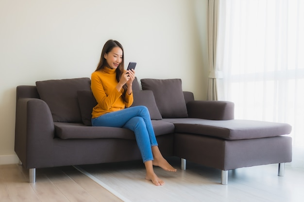リビングルームの枕が付いているソファーでスマートな携帯電話を使用して肖像若いアジア女性