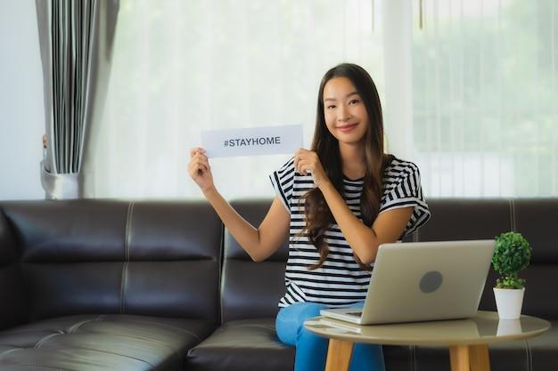 Портрет красивой молодой азиатской женщины используя компьтер-книжку на софе с бумагой пребывания дома