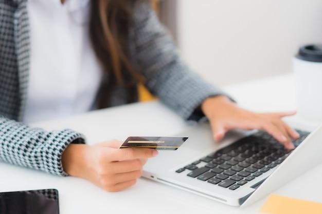 Кредитная карточка пользы женщины портрета красивая молодая азиатская с компьтер-книжкой для онлайн покупок