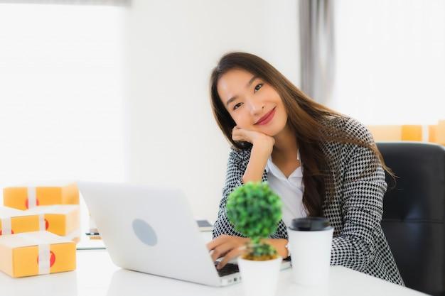 Работа портрета красивая молодая азиатская бизнес-леди от дома с мобильным телефоном компьтер-книжки с картонной коробкой готовой для грузить