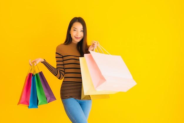 Улыбка красивой молодой азиатской женщины портрета счастливая с много хозяйственной сумкой цвета от универмага на желтой стене