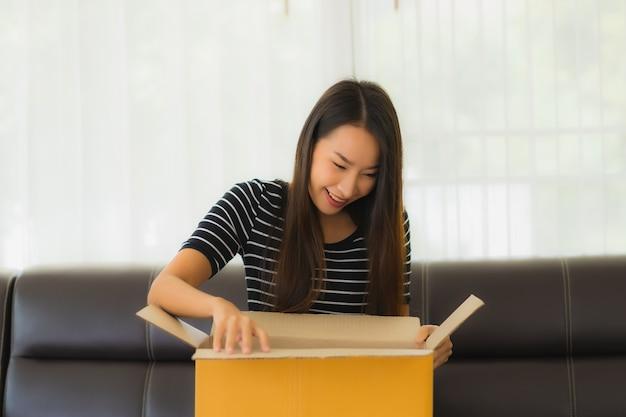 Портрет красивой молодой азиатской женщины с картонной коробкой