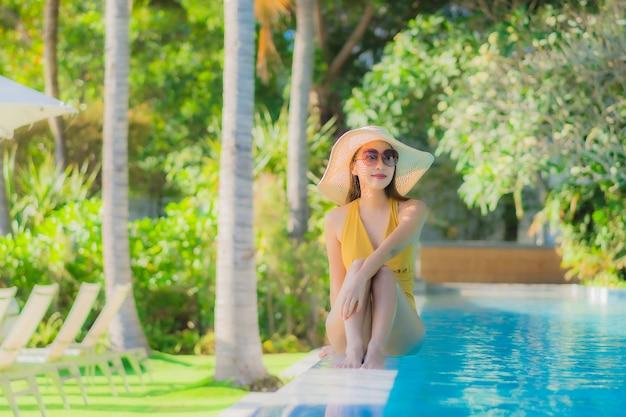 美しい若いアジア女性の幸せな笑顔は、ホテルリゾートの屋外スイミングプールの周りリラックスします。