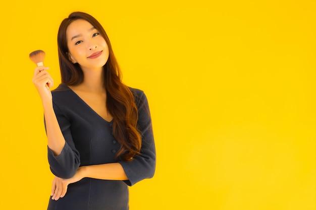化粧筆を持つ若いアジア女性