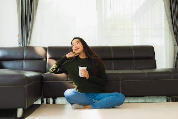 Мобильный телефон красивой молодой азиатской пользы женщины портрета умный с кофейной чашкой
