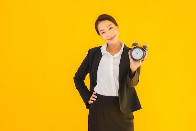 肖像画の美しい若いアジア女性は時計やアラームを表示します。