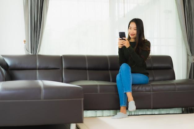 肖像画の美しい若いアジアの女性はスマートな携帯電話や携帯電話を使用します。