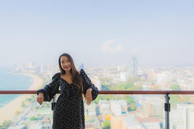 美しい若いアジア女性の肖像画はパタヤシティービューのバルコニーの周りの幸せな笑顔をリラックスします。