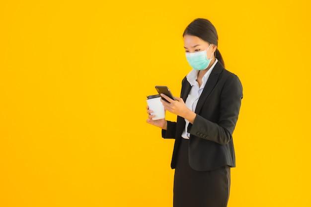 肖像画の美しい若いビジネスアジアの女性着用マスクコーヒーと携帯電話を使用します。