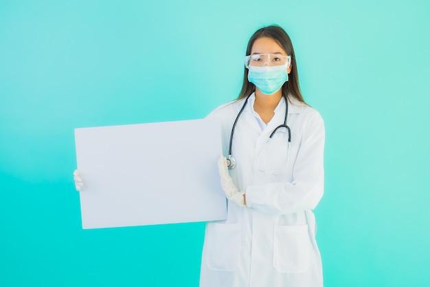 空のカードボードと美しい若いアジア医師女性の肖像画
