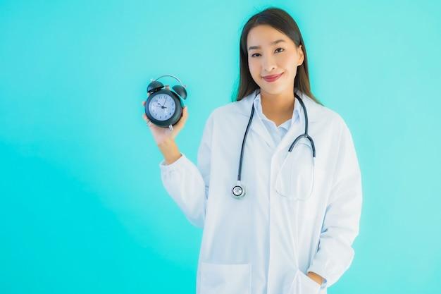 目覚まし時計で若いアジア女性医師