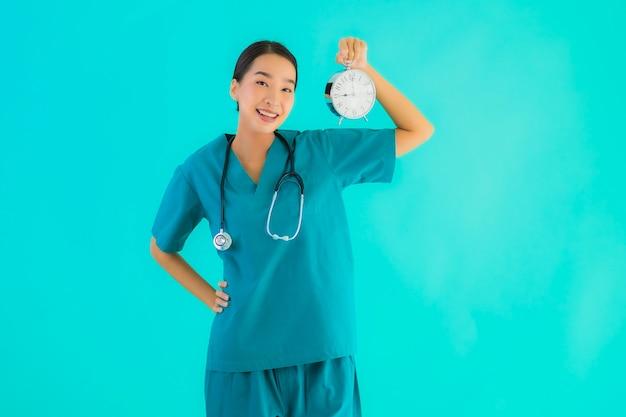Молодая азиатская женщина доктора показывает часы