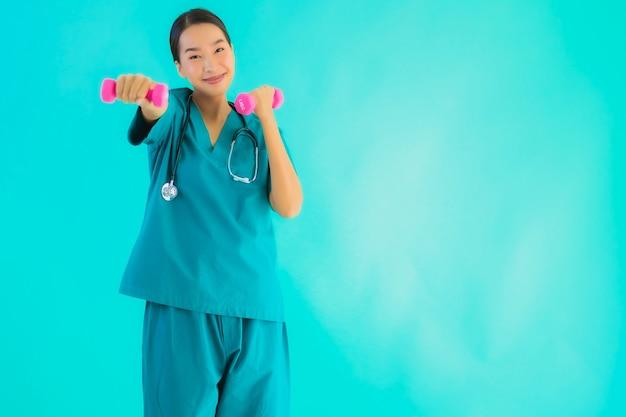 ダンベルの若いアジア医師女性演習