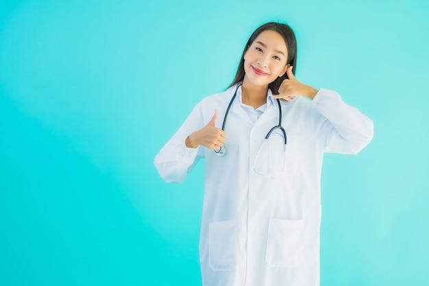 肖像画の美しい若いアジア医師の女性はモバイルスマート携帯電話を使用します。